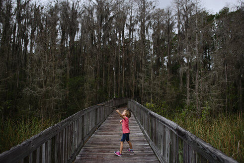 Side view of girl playing with dried branch while standing on boardwalk against forest - CAVF10453