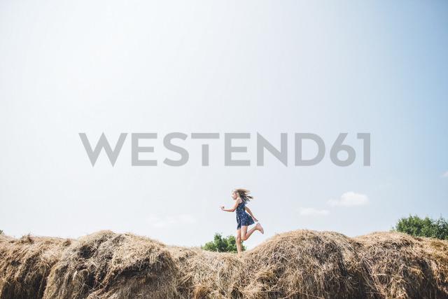 Carefree girl running on heap of hay against sky - CAVF10468