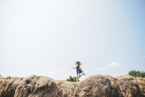 Carefree girl running on heap of hay against sky - CAVF10468