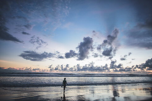 Rear view of woman standing on beach against cloudy sky during sunset - CAVF10474