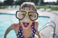 Portrait of girl with mouth open wearing swimming goggles while standing on poolside - CAVF10477