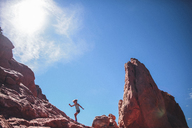 Low angle view of carefree girl climbing on rock formation against sky - CAVF10489