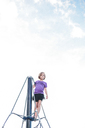 Low angle view of girl standing on outdoor play equipment against cloudy sky at playground - CAVF10495