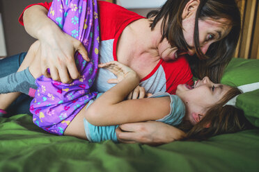Playful mother playing with daughter lying on bed at home - CAVF10501