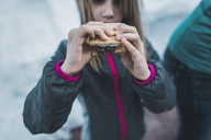 Midsection of girl holding smore on snowy field - CAVF10513