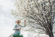 Low angle view of girl picking flowers from tree - CAVF10516