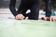 Close-up of woman examining surfboard - CAVF10543