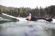 Portrait of woman lying on surfboard in sea - CAVF10546