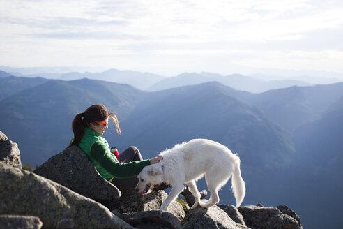 Hiker stroking dog while relaxing on rocks against mountain range - CAVF10555