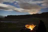 Hiker sitting by campfire against cloudy sky - CAVF10582