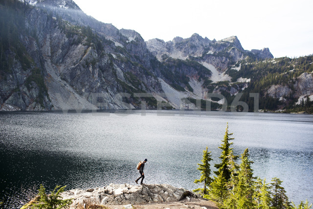 Side view of hiker walking on rocks by Snow Lake - CAVF10594