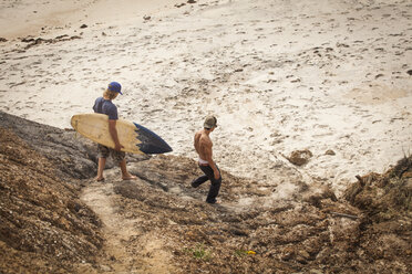 Man carrying surfboard while walking with friend at beach - CAVF10661