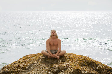 Relaxed man sitting on rock at beach - CAVF10664