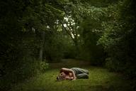 Man sleeping on grassy field in forest - CAVF10670