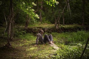 Man sitting on field in forest - CAVF10691