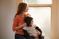 Mother and daughter looking through window while sitting at home - CAVF10721