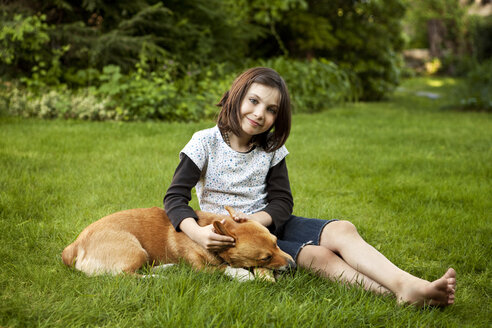 Portrait of girl sitting with dog on grassy field in yard - CAVF10730
