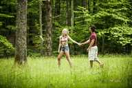 Couple holding hands while walking on grassy filed - CAVF10751