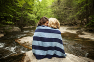 Couple wrapped in towel sitting on rocks in river - CAVF10760