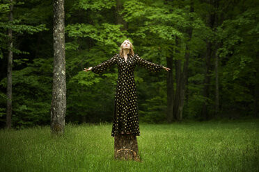 Woman with arms outstretched standing on tree stump in forest - CAVF10769