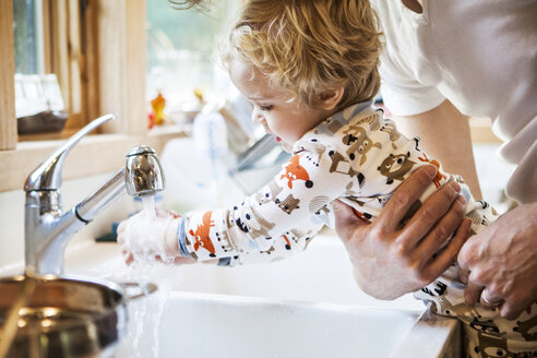 Cropped image of father holding son while washing hands at kitchen sink - CAVF10856