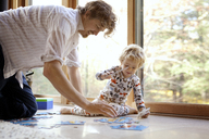Father and son arranging jigsaw puzzle at home - CAVF10868