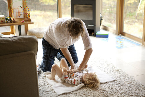 Father changing diaper of son at home - CAVF10877