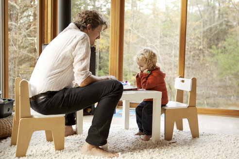 Father and son sitting on chairs at home - CAVF10898