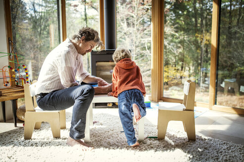 Father teaching son to write while sitting on chair at home - CAVF10901