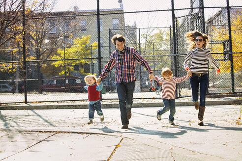 Happy family running in park - CAVF10979