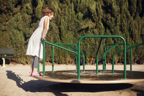 Girl standing on merry-go-round at park - CAVF11015