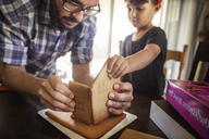Father and son making gingerbread house at home - CAVF11054