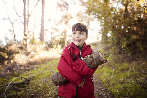 Boy looking away while holding log at forest - CAVF11105