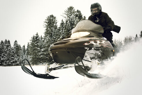 Man riding snowmobile on snow field in forest - CAVF11213