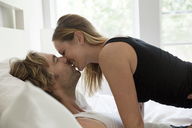 Side view of couple kissing while lying on bed at home - CAVF11228