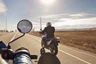 Cropped image of biker with friend riding on road against sky - CAVF11297