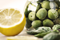 Close-up of green olives in jar on cutting board - CAVF11513