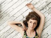 Overhead view of woman looking away while lying on floorboard - CAVF11615