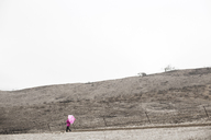 Distant view of girl walking with umbrella on field against clear sky - CAVF11687