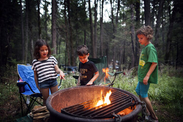 Children standing around fire pit in forest - CAVF11783