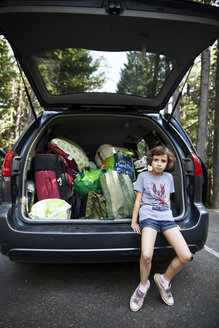 Portrait of girl sitting on car trunk at road - CAVF11795