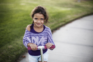 Portrait of girl riding push scooter at park - CAVF11849