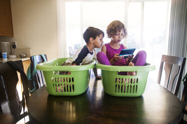 Children using handheld video game while sitting in baskets at home - CAVF11852