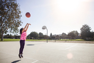 Girl jumping while throwing basketball on court - CAVF11870