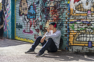 Young man with headphones sitting in front of graffiti wall using cell phone - AFVF00312