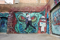 Young man with headphones jumping   in the air in front of graffiti - AFVF00321