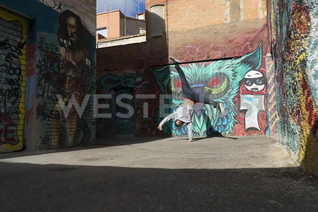 Young man doing handstand on one hand in front of graffiti - AFVF00324