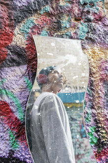 Mirror image of young man with headphones looking at graffiti - AFVF00327