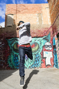 Young man with headphones jumping in the air in front of graffiti - AFVF00330