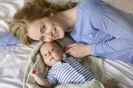 Portrait of smiling mother with her baby boy lying on bed - BMOF00065